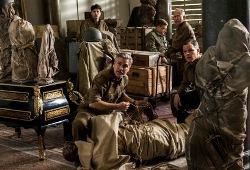 Matt Damon e George Clooney con Hugh Bonnebille, John Goodman e Bob Balaban sullo sfondo in Monuments Men